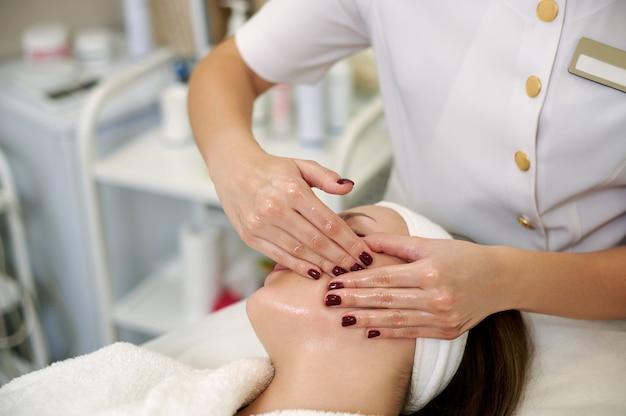 Cosmeticista fazendo massagem de lifting facial para bela jovem em salão de spa