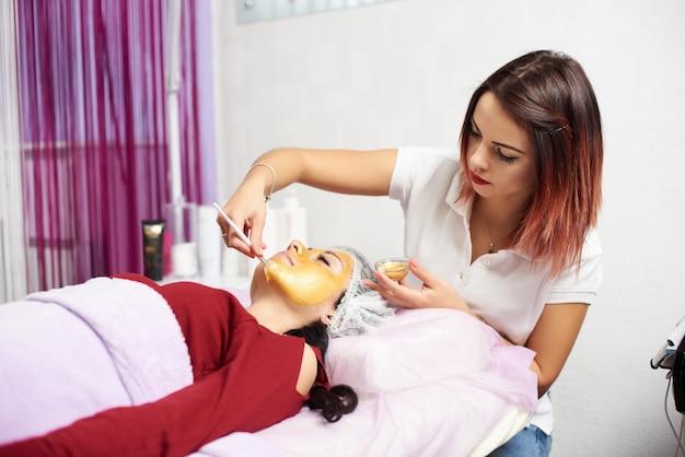 Cosmeticista fazendo procedimento em rosto de mulher
