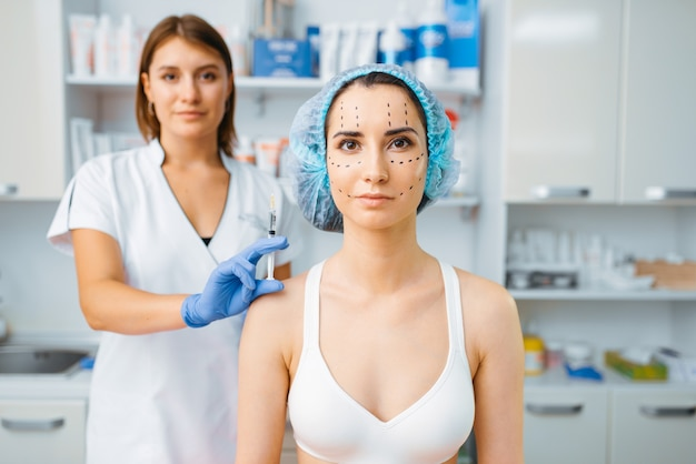 Cosmeticista segura seringa de botox e paciente do sexo feminino com marcadores no rosto. procedimento de rejuvenescimento em salão de esteticista. cirurgia cosmética contra rugas e envelhecimento