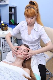 Cosmeticista trabalhando em um salão de beleza. ela faz massagem facial com sotaque no pescoço