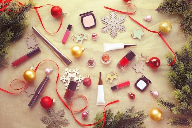 Cosmético de maquiagem colorida com decoração de natal na mesa de madeira, vista superior