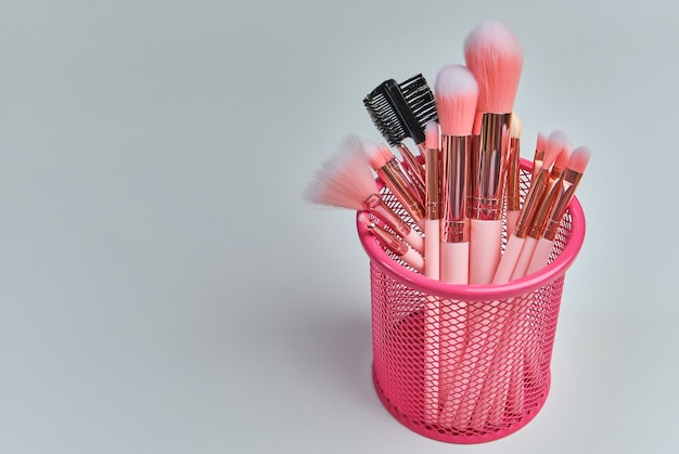 Cosmético profissional rosa pincéis de maquiagem em uma caixa rosa em um fundo branco com espaço livre.