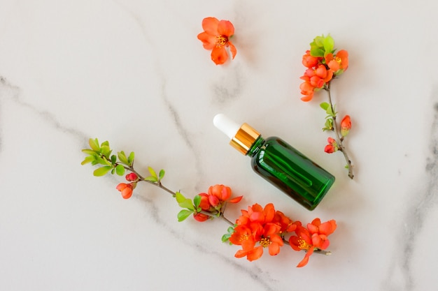 Cosmético spa orgânico com ingredientes herbais. soro com extratos de ervas para o cuidado da pele. cosméticos da natureza em frasco de vidro com pipeta e flores sobre fundo de mármore.