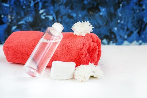 Cosmético tônico e toalha. o conceito de cosméticos e beleza.