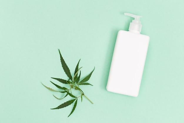 Cosméticos à base de cannabis, frasco com loção ou gel para o corpo e folha natural de cannabis.