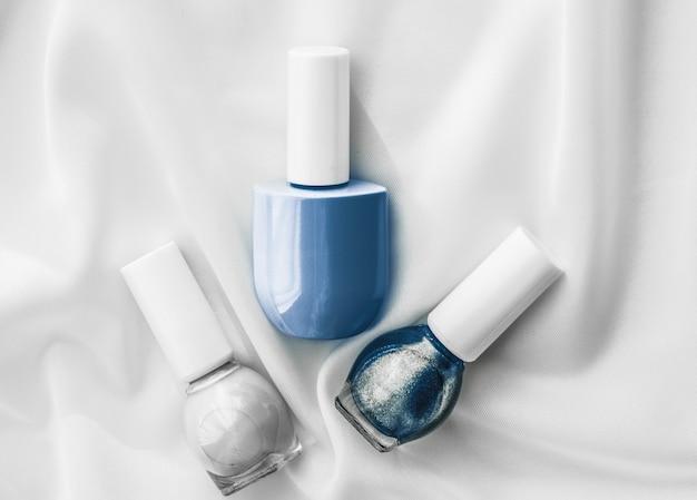 Cosméticos branding salão e glamour conceito unha polonês garrafas em seda fundo manicure francesa ...