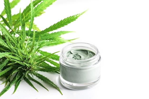 Cosméticos cbd. planta e frasco de cannabis verde com um creme hidratante de rejuvenescimento.