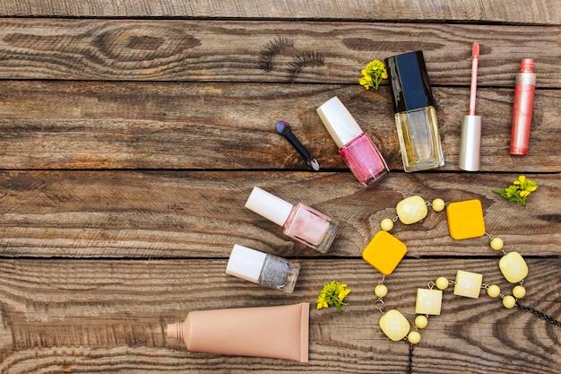 Cosméticos :, cílios postiços, corretivo, esmalte, perfume, brilho labial, miçangas e flores amarelas em fundo de madeira. imagem enfraquecida.