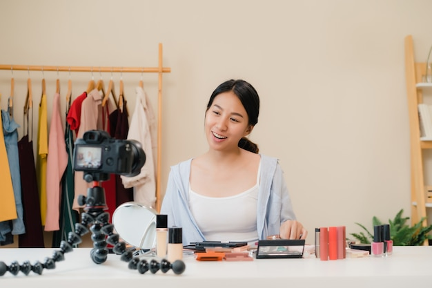Cosméticos da beleza do presente do blogger da beleza que sentam-se na câmera dianteira para gravar o vídeo.