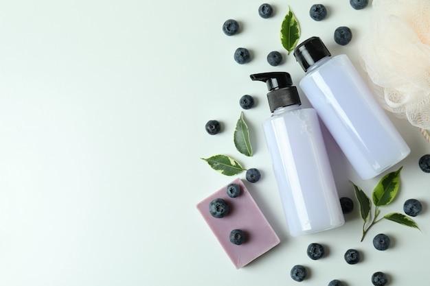 Cosméticos de banho naturais e mirtilo em fundo branco
