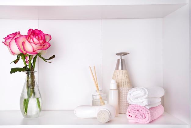 Cosméticos de banho spa e flor rosa, isolado no branco