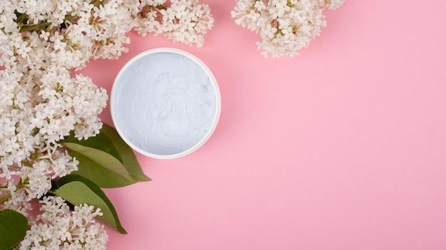 Cosméticos de corpo branco sobre um fundo rosa com galhos de um espaço de cópia de florescência lilás branco close-up, cuidados com a pele, beleza, esfoliação.