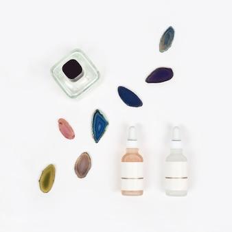 Cosméticos de farmácia orgânica com pedra natural de ágata em fundo branco vista plana de cima produtos de beleza naturais para conceito de maquete de marca