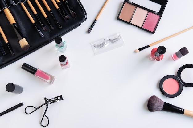 Cosméticos de mulher, escova e maquiagem no fundo branco