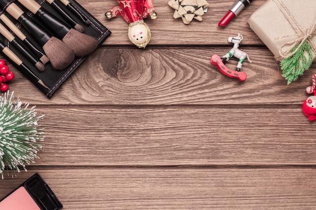 Cosméticos de mulher, pincéis de maquiagem, batom e enfeites de natal em madeira
