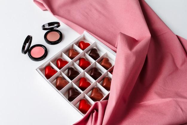 Cosméticos decorativos e chocolate sobre a superfície branca