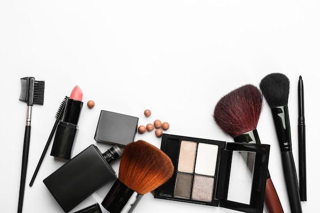 Cosméticos decorativos e ferramentas de maquiador profissional em fundo branco