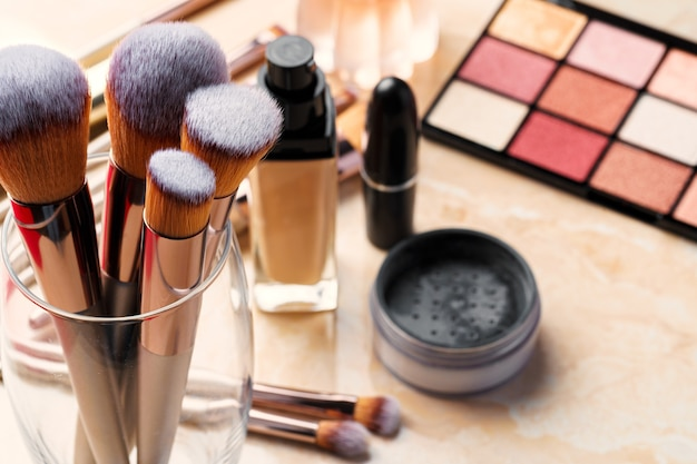 Cosméticos decorativos e ferramentas na penteadeira na sala de maquiagem, close-up