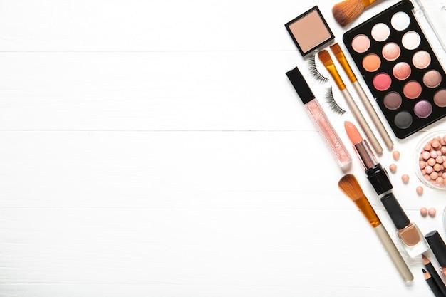 Cosméticos decorativos e pincéis de maquiagem em uma parede branca, vista superior. lugar para texto