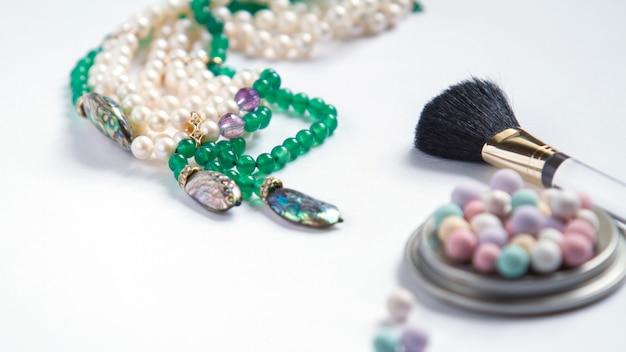 Cosméticos e jóias de pérolas no fundo branco