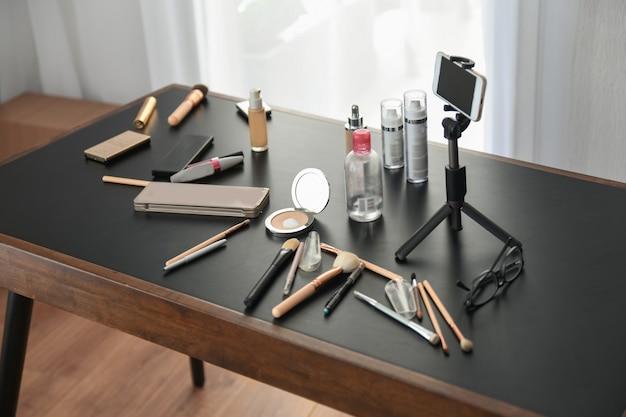 Cosméticos e pincéis de maquiagem na mesa do blogueiro