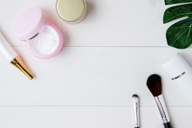 Cosméticos e produtos de cuidados da pele e folhas verdes na mesa de madeira branca