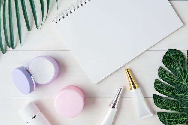 Cosméticos e produtos de cuidados da pele e notebook e folhas na mesa