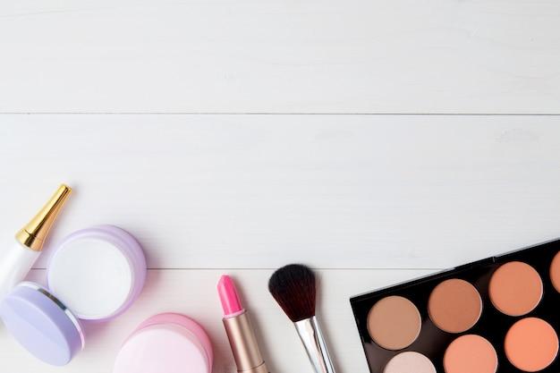 Cosméticos e produtos de cuidados da pele na mesa de madeira branca
