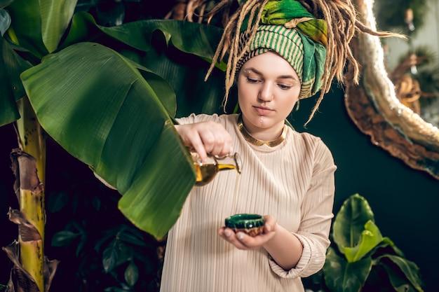 Cosméticos ecológicos. mulher jovem preparando produtos de beleza naturais e parecendo ocupada