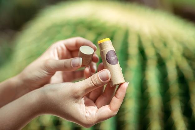 Cosméticos ecológicos. perto das mãos da mulher segurando um protetor labial