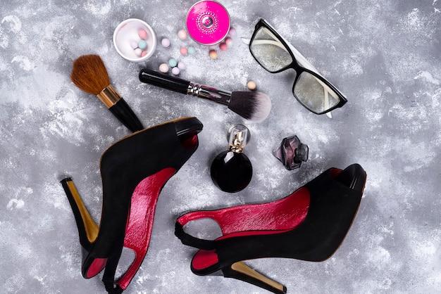 Cosméticos em perfume e sapatos em um fundo cinza com espaço de cópia