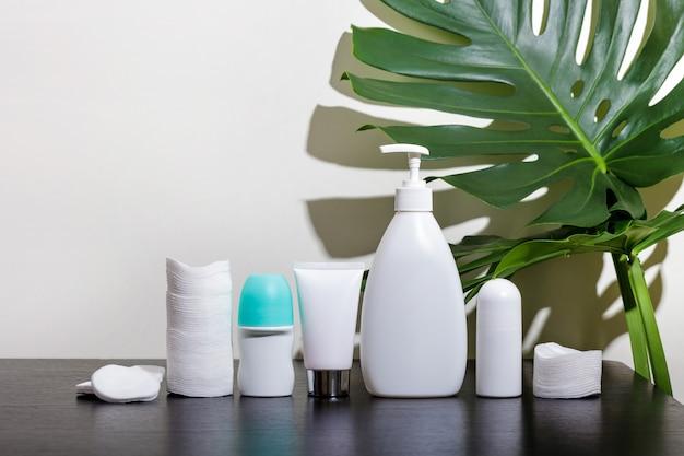 Cosméticos em tubos brancos e produtos de banho em uma mesa preta com folhas tropicais.