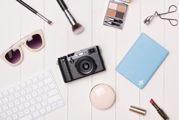 Cosméticos femininos e artigos de moda na mesa com câmera e passaporte. vista do topo