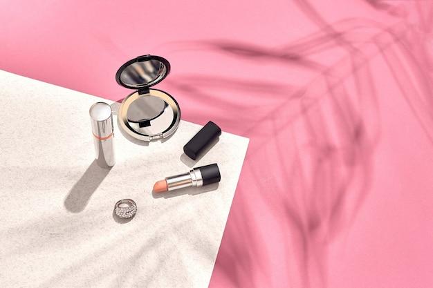 Cosméticos femininos elegantes e acessórios planos de sombra de fundo rosa e branco de uma folha de palmeira