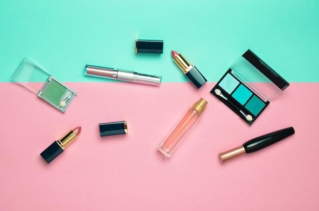 Cosméticos femininos para layout de maquiagem. sombras cosméticas, pincel de maquiagem, batom da sombra, frasco de perfume. vista plana leiga, superior. copie o espaço.