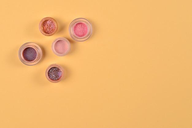 Cosméticos. inventar. frascos com sombras brilhantes esfareladas, glitter. cores rosa, pêssego e douradas sobre fundo bege. fechar-se. espaço para texto ou desenho.