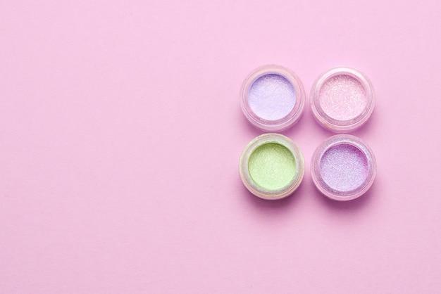 Cosméticos. inventar. frascos com sombras brilhantes esfareladas, glitter. cores rosa, verdes e lilás em fundo lilás. fechar-se. espaço para texto ou desenho.