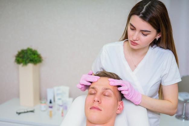 Cosméticos masculinos. homem bonito recebendo tratamento facial em spa de luxo