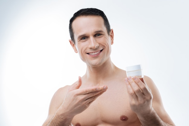 Cosméticos masculinos profissionais. jovem alegre e agradável sorrindo e olhando para você enquanto apresenta um creme facial