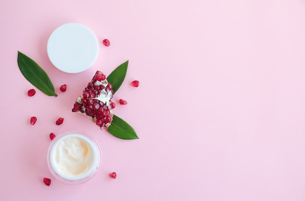 Cosméticos naturais com ácidos de frutas, com extrato de romã em um fundo rosa. logotipo, plana leigos, modelo, banner, em branco, copie o espaço. conceito de beleza