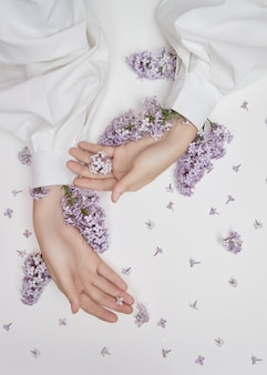 Cosméticos naturais de mulher para mãos feitas de pétalas e flores lilás. hidrate e suavize a pele das mãos. flores lilás projetam-se das mangas do braço