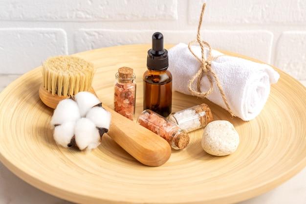Cosméticos naturais em embalagem ecológica em placa de bambu com flor ctton e toalha. spa, produtos de beleza para banho.