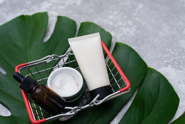 Cosméticos naturais em uma cesta de compras no fundo de uma folha de palmeira. cosméticos naturais. copie o espaço. postura plana.