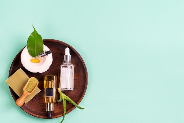 Cosméticos naturais, óleos para a pele e sabão natural com folhas e aloe vera em uma placa de madeira em um azul