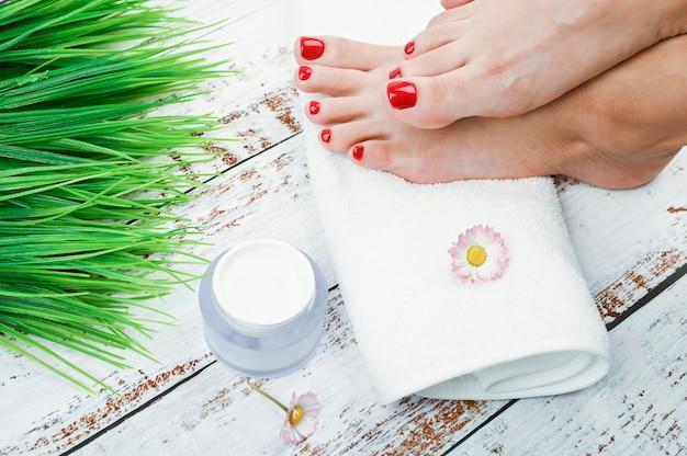 Cosméticos naturais para as pernas. o conceito de cosméticos ambientais e naturais para a pele das pernas. pés das mulheres em uma toalha