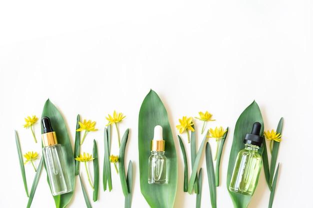Cosméticos orgânicos de beleza natural e óleos para cuidados com a pele na parede com folhas e flores. soro anti-envelhecimento em frasco de vidro com conta-gotas. soro líquido facial com colágeno e peptídeos.
