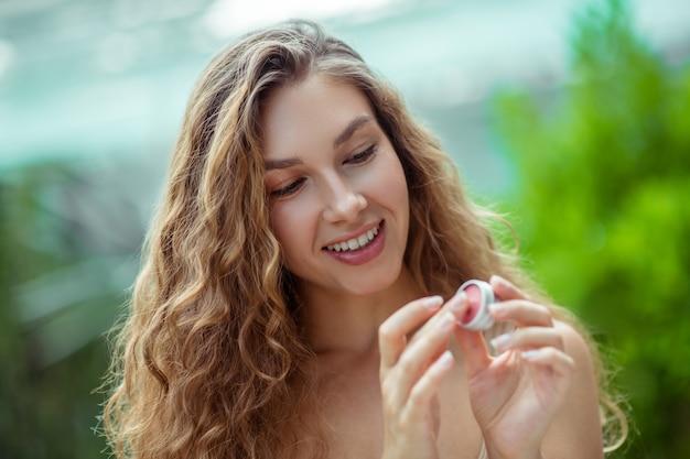 Cosméticos orgânicos. jovem bonita segurando um protetor labial na mão