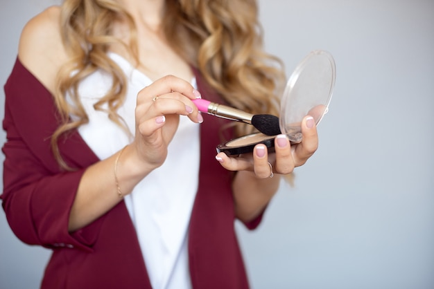 Cosméticos para a beleza. close-up de uma jovem bonita com maquiagem glamourosa, penteado elegante, segurando um pincel de maquiagem.