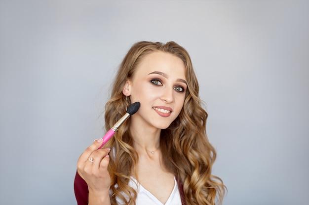 Cosméticos para a beleza. cosméticos. close-up de uma jovem bonita com maquiagem glamourosa, penteado elegante, segurando um pincel de maquiagem.