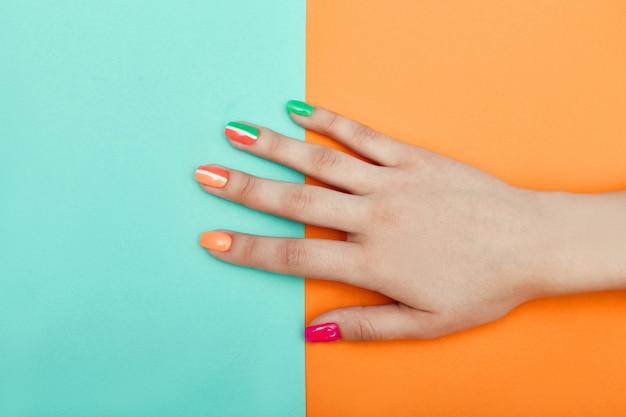 Cosméticos para as mãos, unhas para colorir e cuidar, manicure profissional e produtos para cuidados. mão deitada em um papel colorido
